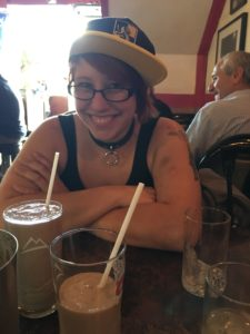 my adorable friend Bex smiling and drinking a milkshake