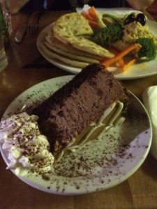 a slice of dulce de leche cheesecake and a plate of hummus and veggies