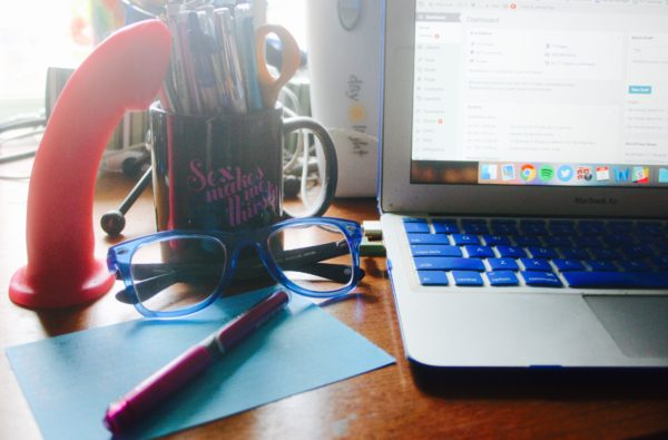 a dildo, mug full of pens, pair of glasses, and laptop on my desk