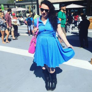 me wearing a blue polka-dotted dress and sunglasses in a busy New York square